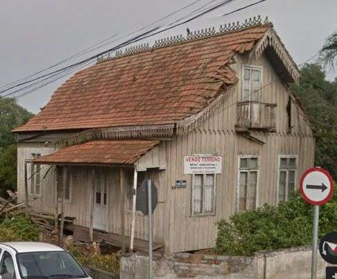 Casa com lambrequim na beira do telhado, varanda em uma das laterais e sacada na parte superior.