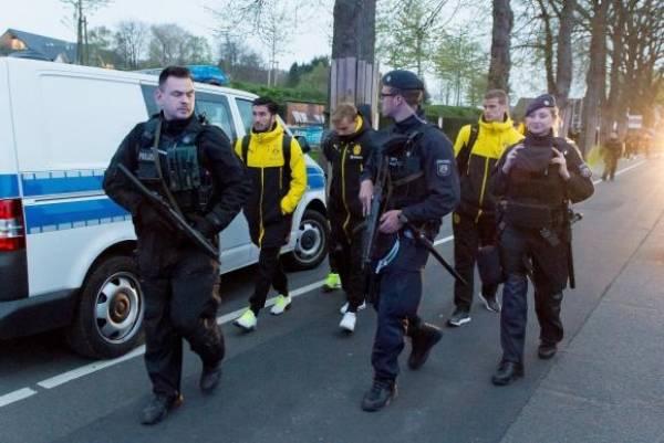 Jogadores do Borussia Dortmund são escoltados pela polícia após a explosão. Foto: STR/Agência Lusa