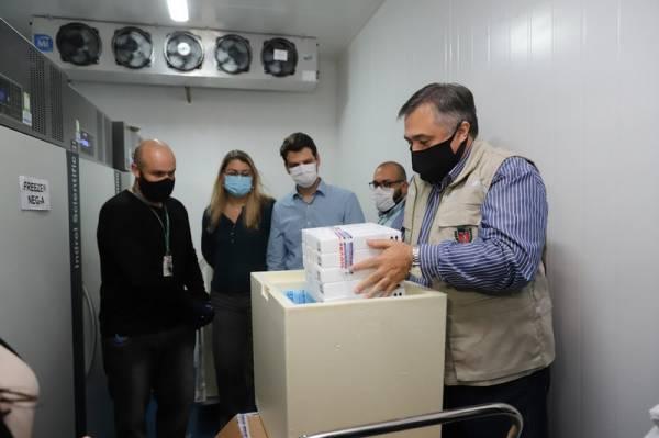 O Secretário de Estado da Saúde, Beto Preto e o vice-prefeito Eduardo Pimentel recebem o primeiro lote de 32.760 doses de vacinas contra a Covid-19 da Pfizer no Centro de Medicamentos do Paraná (Cemepar), em Curitiba, na noite desta segunda-feira (3). Foto: Geraldo Bubniak/AEN
